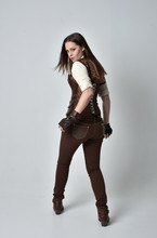 Full Length Portrait Of Brunette  Girl Wearing Brown Leather Steampunk Outfit. Standing Pose With Back To The Camera, On Grey Studio Background.