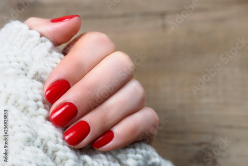 Female hand with red manicure on a white knitted background with copy space, top Fototapeta