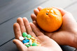 Humans hands with pills and mandarin fruit. Male hand holding pills and fruits. Vegan choice. Health food. No pills.