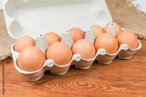 Brown eggs in paper pulp egg carton on rustic table