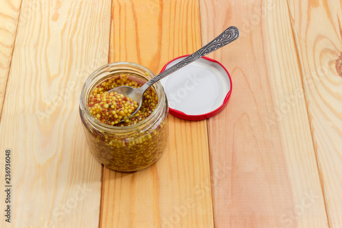Fotobehang Kruiderij French mustard on spoon in glass jar on wooden surface
