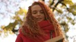 Close up of red curly head pleased woman sitting on bench and reading book in park. Footage from the low angle. Autumn sky and yellow leaves trees on the blurred background