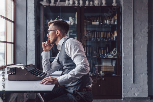 Thinking young man with a retro typewriter