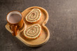 Sweet roll with cream with hot milk chocolate on a wooden heart-shaped tray