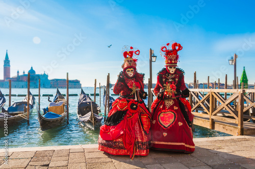 Couple wearing venitian carnival mask in front of gondolas in Grand Canal during Venice carnival in Italy