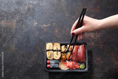Fototapeta Obiad na wynos, tacka sushi. Jedzenie sushi pałeczkami prosto z tacki. obraz