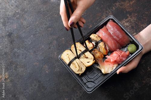 Fototapeta Sushi na wynos.  Jedzenie sushi pałeczkami prosto z tacki. obraz