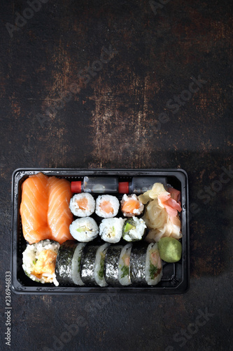 Fototapeta Sushi na wynos. Tacka z kawałkami sushi , imbirem , wasabi i sosem sojowym na ciemnym tle. obraz
