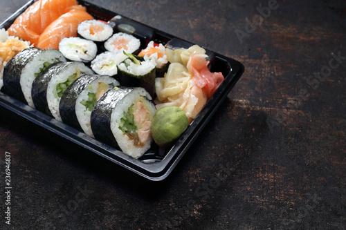 Fototapeta Sushi. Jedzenie na wynos. Tacka z kawałkami sushi , imbirem , wasabi i sosem sojowym na ciemnym tle. obraz