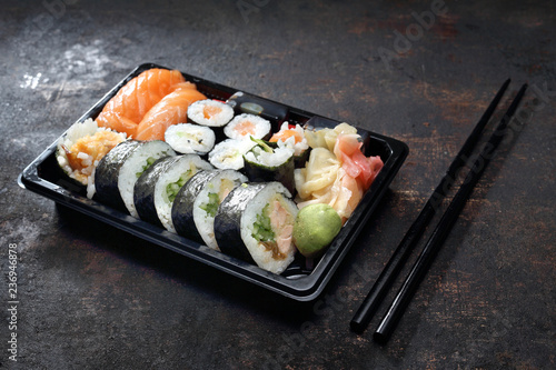 Fototapeta Tradycyjna kuchnia japońska, sushi. Tacka z kawałkami sushi , imbirem , wasabi i sosem sojowym na ciemnym tle. obraz
