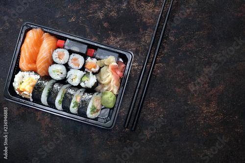 Fototapeta Sushi. Tacka z kawałkami sushi , imbirem , wasabi i sosem sojowym na ciemnym tle w kompozycji z pałeczkami. obraz