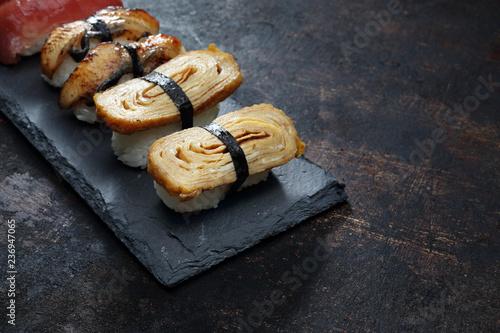Fototapeta Nigiri sushi  na kamiennym talerzu. Sushi.  Kompozycja na ciemnym tle. obraz