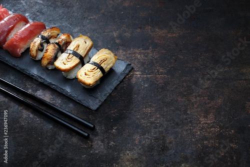Fototapeta Nigiri na kamiennym talerzu. Sushi.  Zestaw sushi. Kompozycja na ciemnym tle. obraz