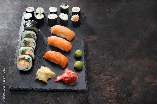 Fototapeta Zestaw sushi. Apetyczne, różnorodne sushi na kamiennym talerzu. Kompozycja na ciemnym tle. obraz