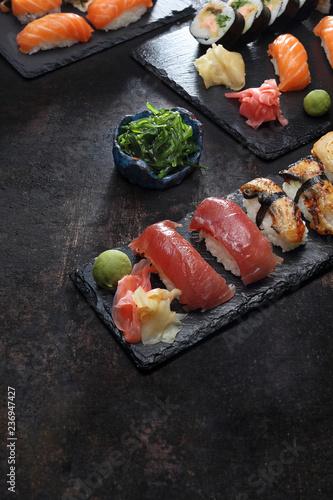 Fototapeta Sushi.  Apetyczne, różnorodne sushi na kamiennym talerzu. Kompozycja na ciemnym tle. obraz