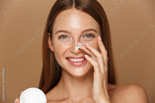 Fotografie, Obraz Beauty image of attractive shirtless woman smiling and holding jar with face cre