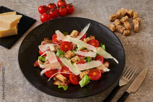 Fotografía  Caesar salad on a black plate, ingredients