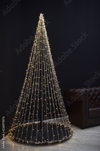 Fotografía  New year's Loft-style decor against a black wall, a Christmas tree from a garland, and brown sofa