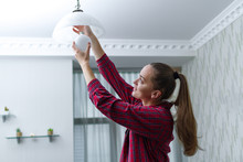 Young, Attractive Housewife Makes The Replacement Of The Used LED Light Bulb In The Chandelier In The Room