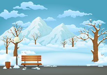 Winter Day Park. Snow Covered Wooden Bench, Trash Bin And Street Lamp On An Asphalt Park Trail With Snowy Mountains In The Background.