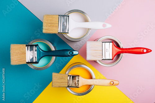 Fotografie, Obraz Four open cans of paint with brushes on them on bright symmetry background