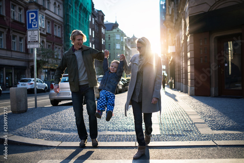 Fotografia, Obraz  A small toddler boy with parents crossing a road outdoors in city at sunset
