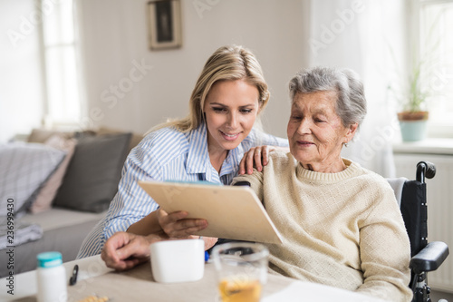 Canvas Print A health visitor measuring a blood pressure of a senior woman at home