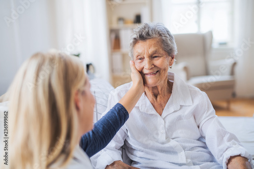 Fotografia  A health visitor talking to a sick senior woman sitting on bed at home