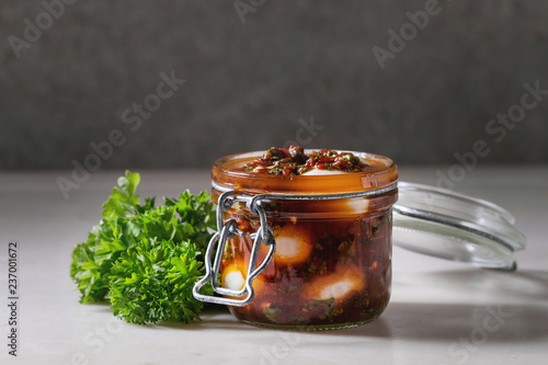 Fotografía Opened Jar with homemade pickled marinated quail eggs in tomato and olive oil sauce with anchovies and fresh parsley on white marble kitchen table
