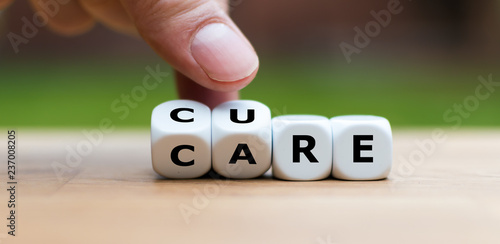 Photo Hand is turning dices and changes the word CARE to CURE