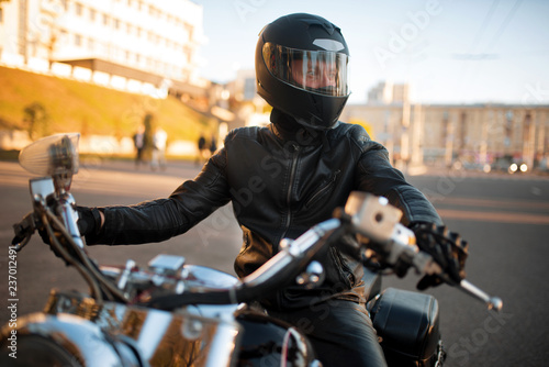 Biker in leather jacket and helmet with visor