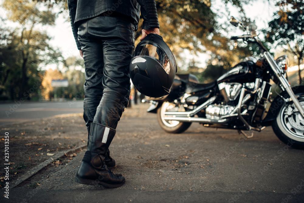 Fototapeta Motorcyclist with helmet in hand goes to chopper