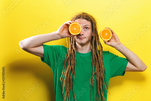 Fotografie, Obraz  Happy young man holding oranges on a yellow background