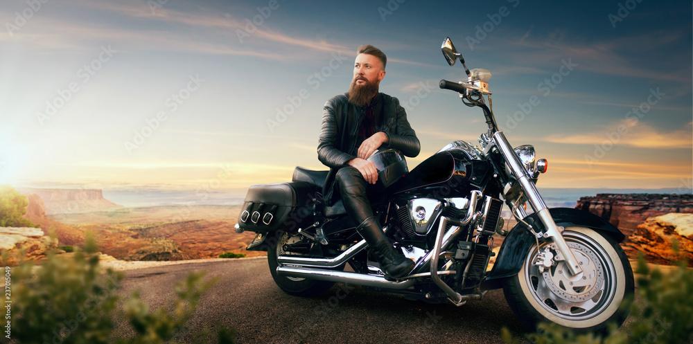 Fototapeta Biker sitting on his chopper and looks on sunset