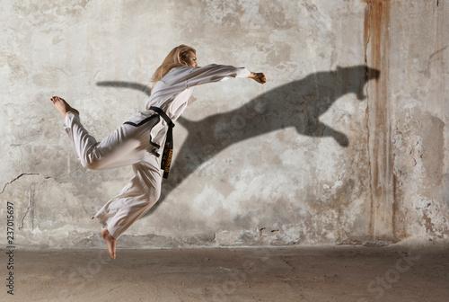 Woman in kimono practicing taekwondo