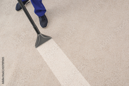 Man removing dirt from carpet with professional vacuum cleaner in room, top view