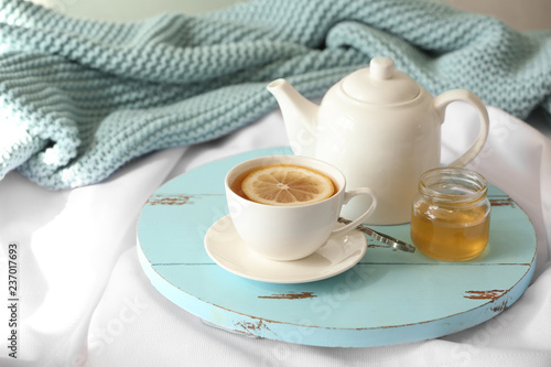 Wooden board with cup of lemon tea and teapot on fabric