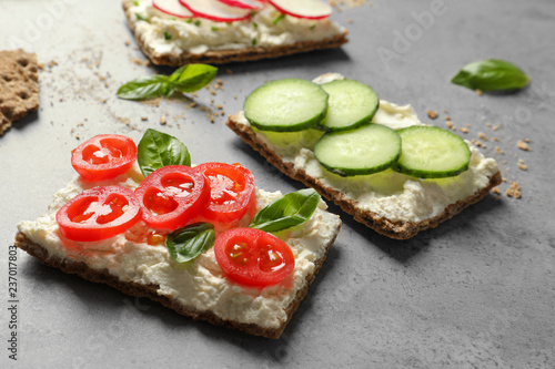 Tasty snacks with cream cheese and vegetables on gray table