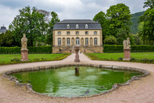 The Abbey Garden In Echternach - The Oldest Town In Luxembourg, With A Fountain And The Building Of The Orangery On An Overcast May Day