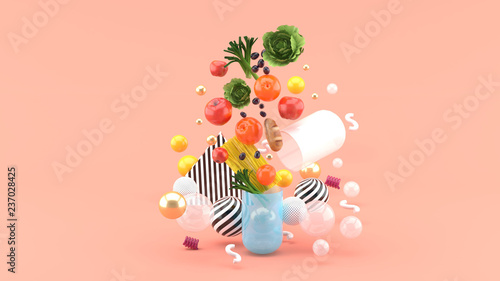 Fotografia  The food floats out of the capsule amidst colorful balls on the pink background