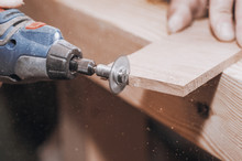Hands Of A Man Holding A Dremel Tool With An Installed Small Circular Saw. Wood Processing. Workshop. Manufacture Of Wooden Products. Joiner's Cutting Tool