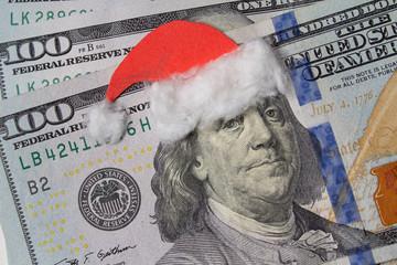 Obraz na płótnie Canvas Benjamin Franklin in a Santa Claus hat on a bill. Christmas decorations