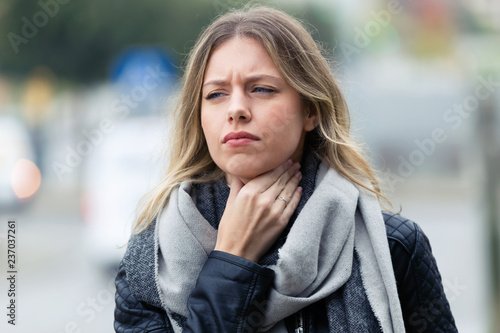 Fotografía Illness young woman with terrible throat pain walking to the street