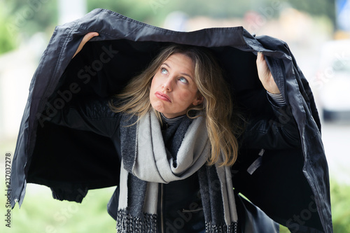 Cuadros en Lienzo Beautiful young worried woman covering herself with her jacket because it's raining in the street