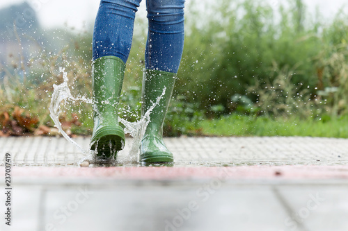 Stampa su Tela Woman in green rubber boots jumping on the puddle water in the street