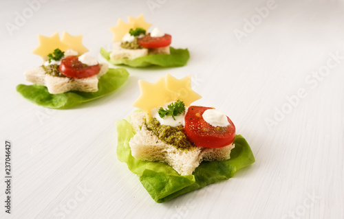 christmas canapes in star shape on lettuce with tomato, pesto and cheese, light background with copy space, close up