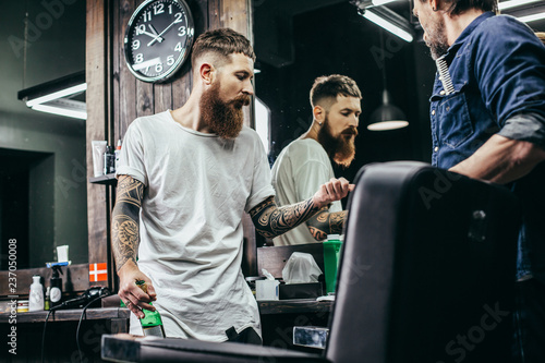 Fotografía  Thoughtful bearded barber showing hair clipper blade to his colleague
