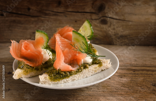 canapes with smoked salmon, cucumber, pesto, cream and dill garnish on a rustic wooden board, copy space, close up