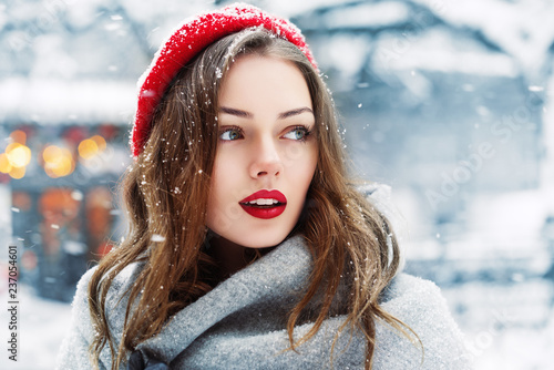 Obraz Outdoor close up portrait of young beautiful fashionable woman with red lips,  wearing woolen beret, scarf, posing in street of european city. Winter fashion, Christmas holidays concept. Copy space - fototapety do salonu