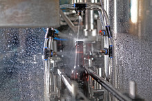 A Bottle Of Beer On A Conveyor Belt Under A Stream Of Water. Only The Bottle Is In Focus. The Concept Of Production.
